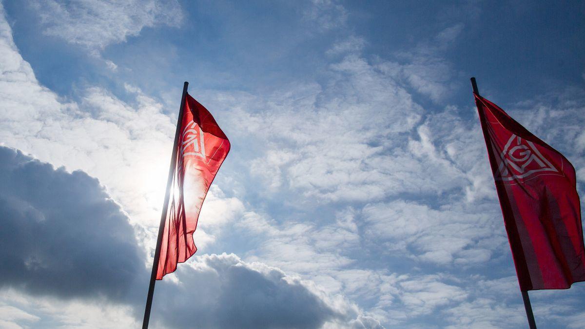 Fahnen der IG Metall vor blauem Himmel mit vereinzelten Wolken.